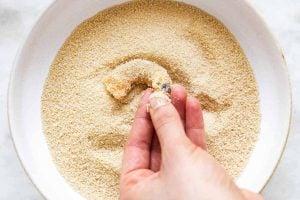 female hand dredging shrimp through breadcrumbs