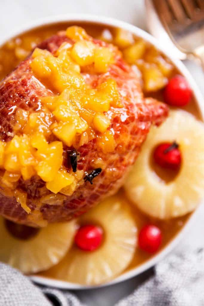 overhead view of pineapple glazed ham on plate with pineapple rings and maraschino cherries