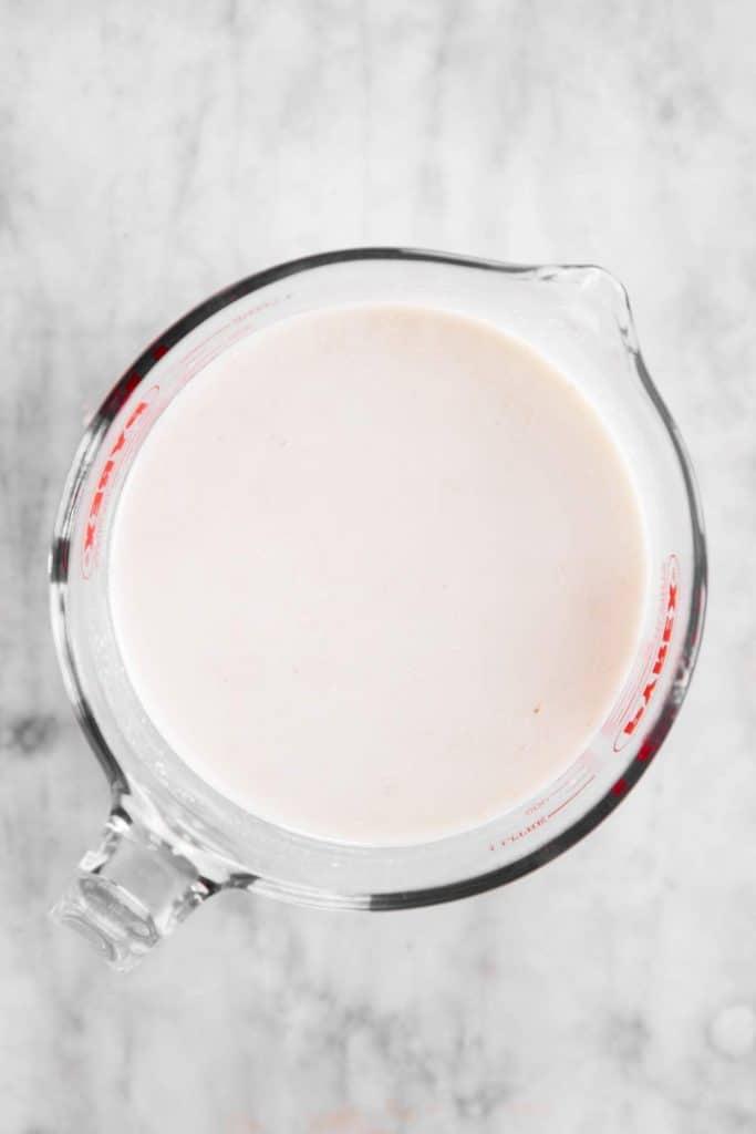 sourdough starter dissolved in water in glass measuring jug