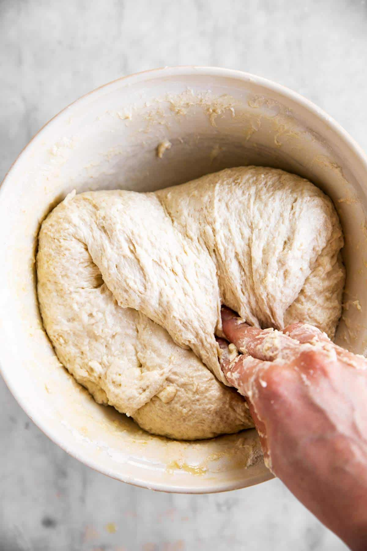 female hand folding sourdough bread dough in white mixing bowl
