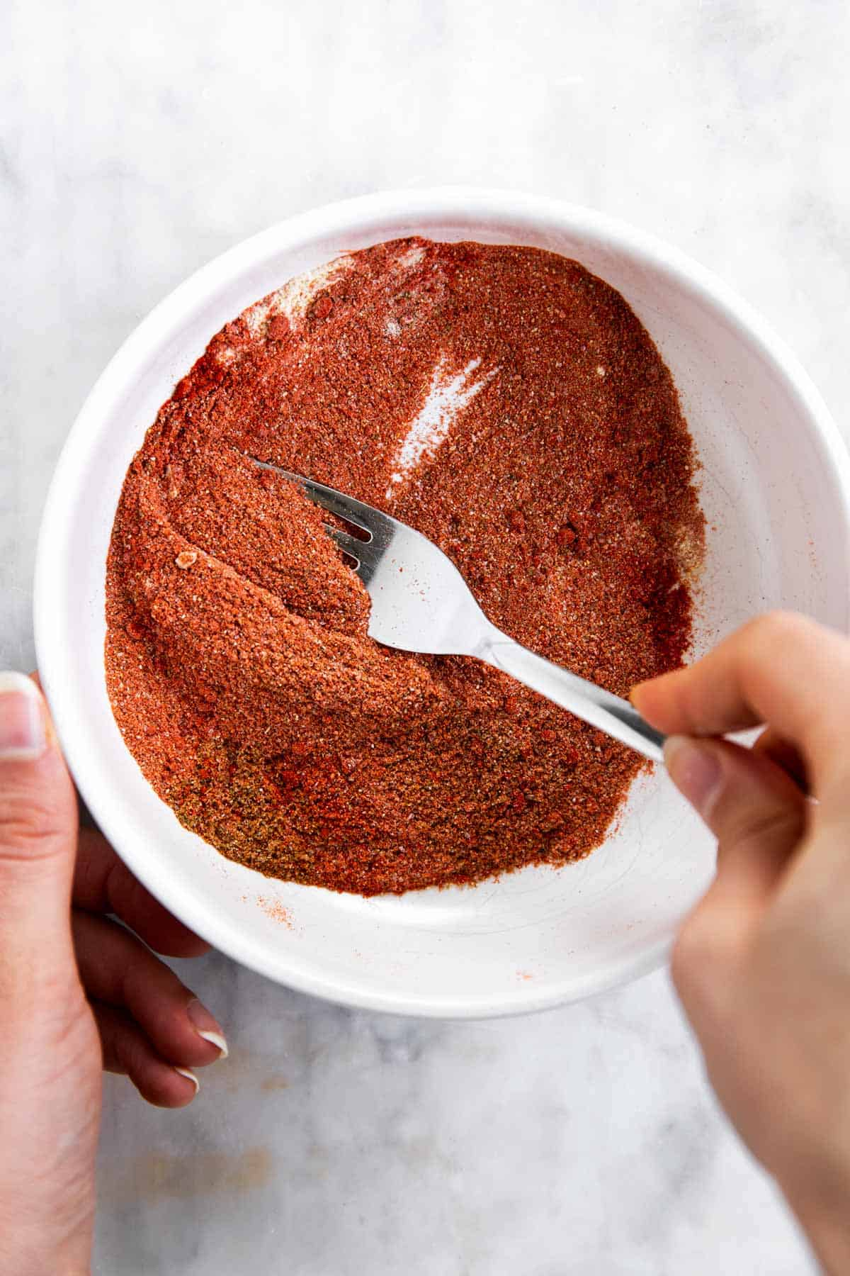 female hands mixing fajita spices with a fork in a white bowl