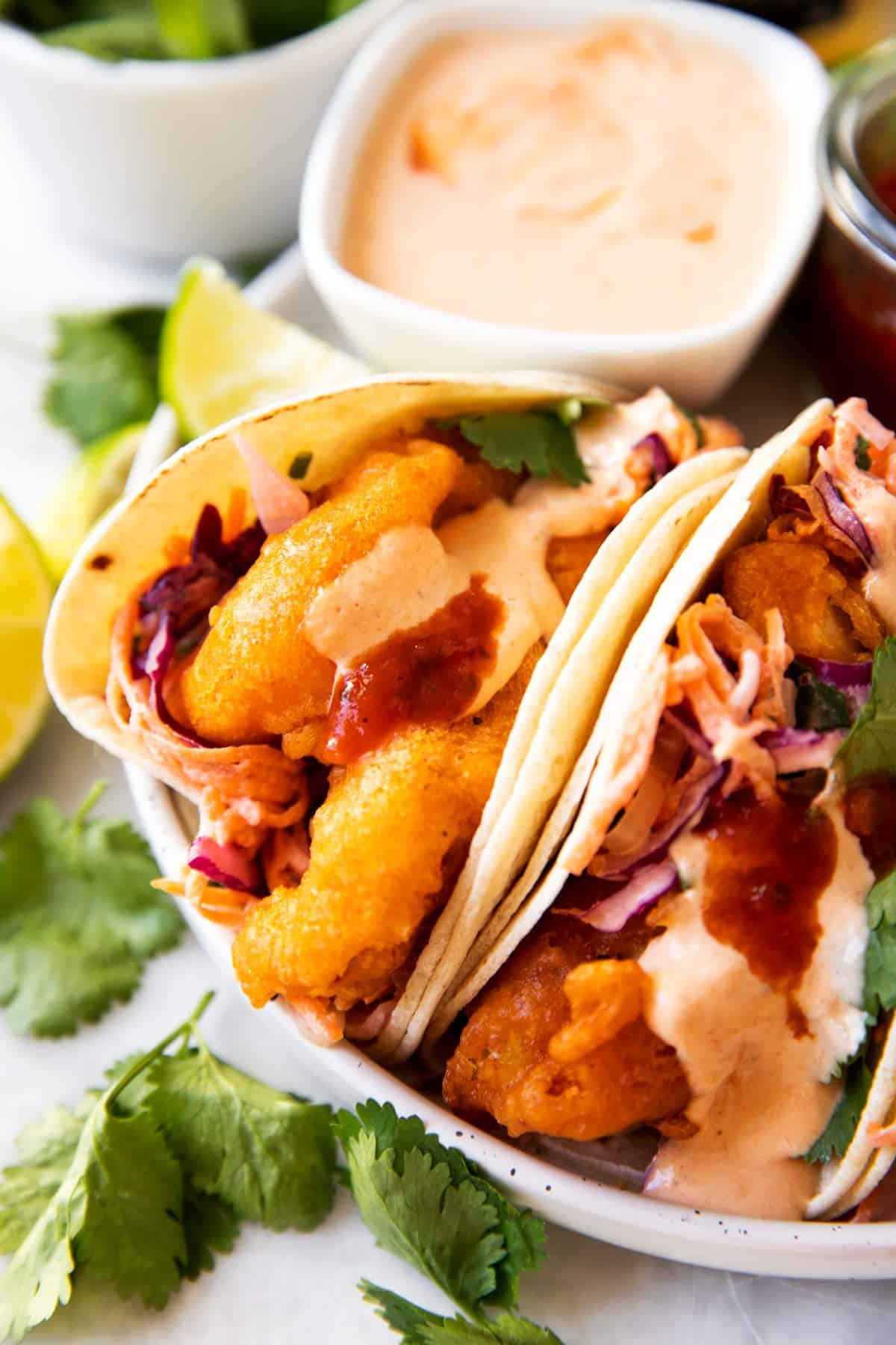 baja fish tacos on a plate with sauces in background
