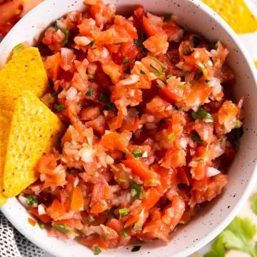 white bowl with chips and fresh salsa inside