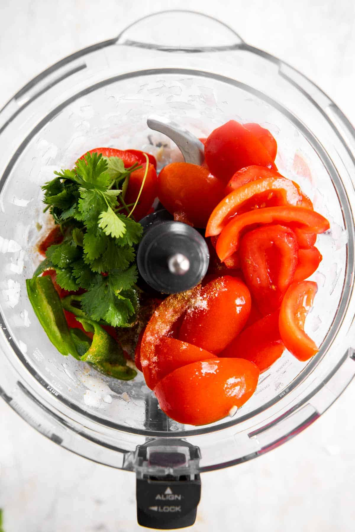 cilantro and tomatoes in food processor bowl