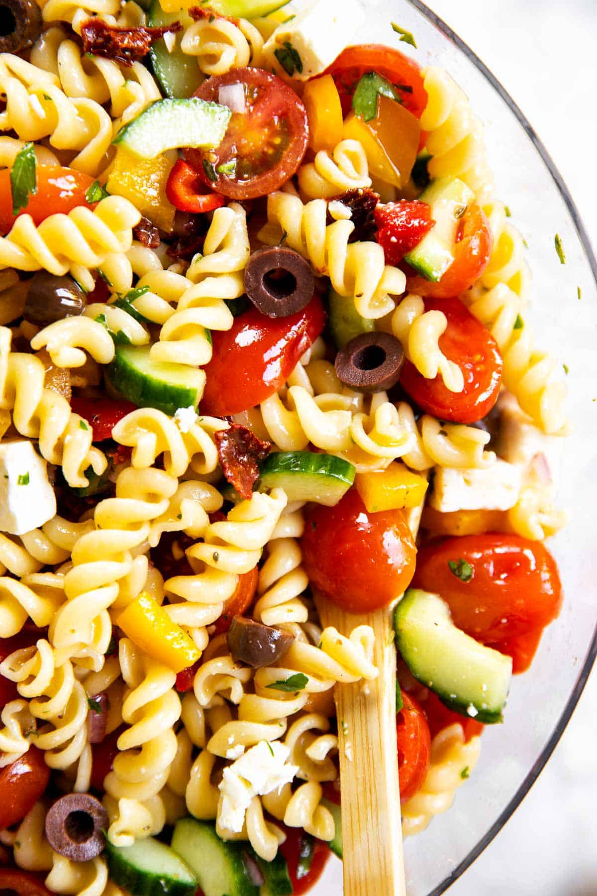 close up photo of greek pasta salad in glass bowl with wooden spoon
