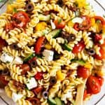 overhead view of greek pasta salad in glass bowl
