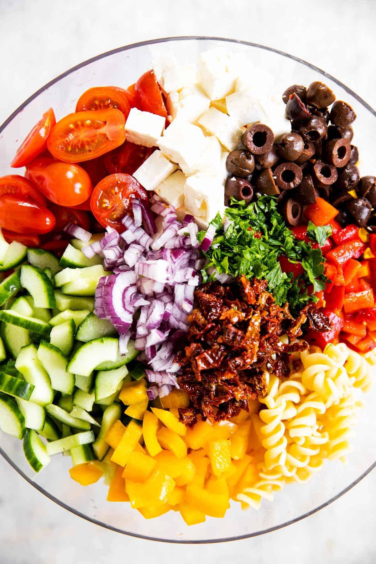 ingredients for greek pasta salad in glass bowl