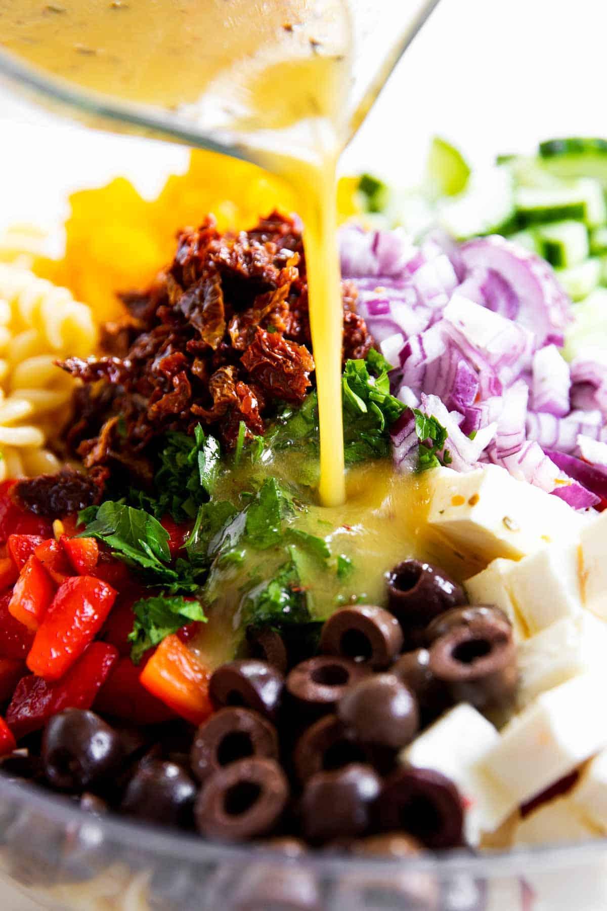 Greek salad dressing pouring over salad ingredients for Greek pasta salad