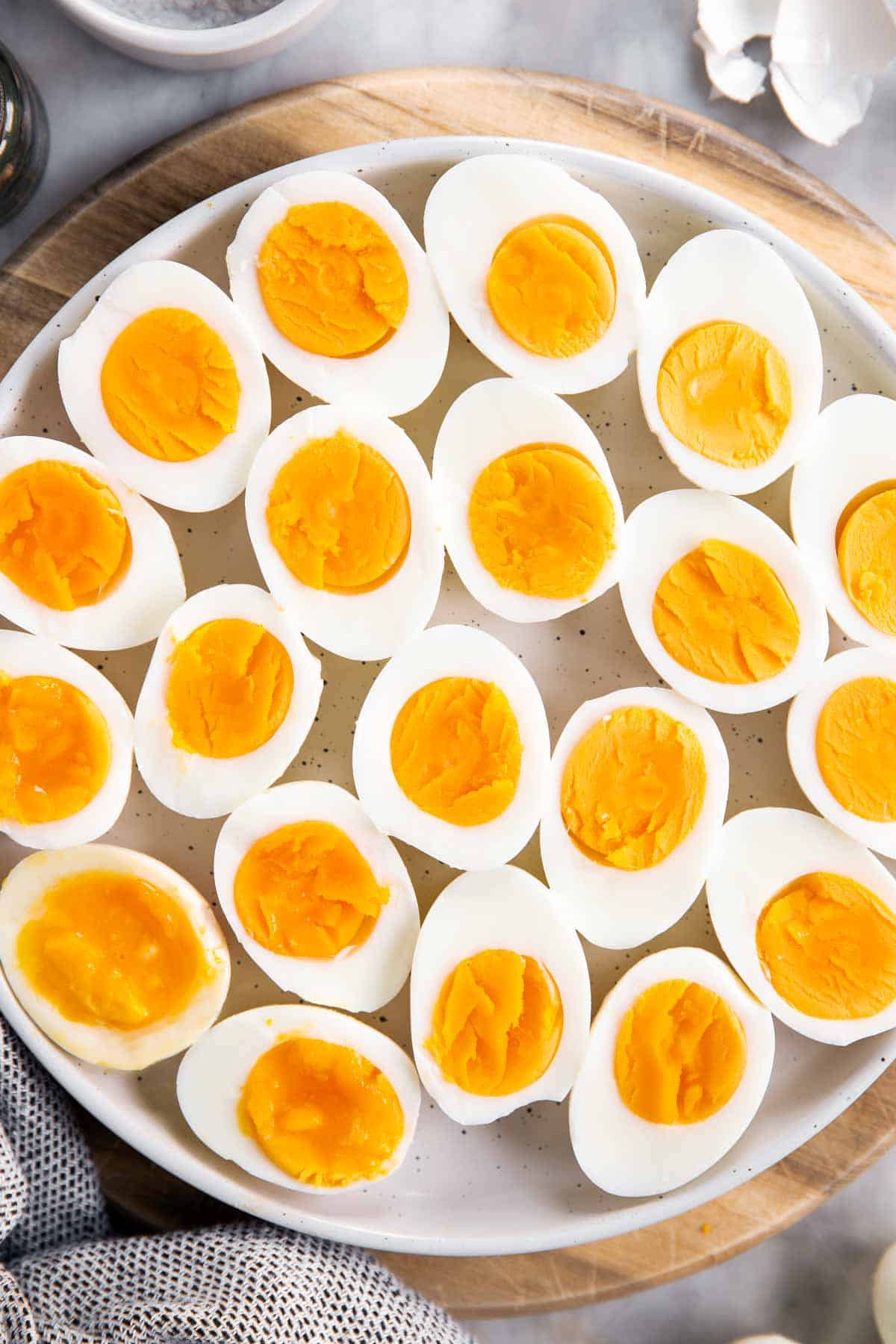 overhead closeup of white platter with hard boiled eggs cut in halves