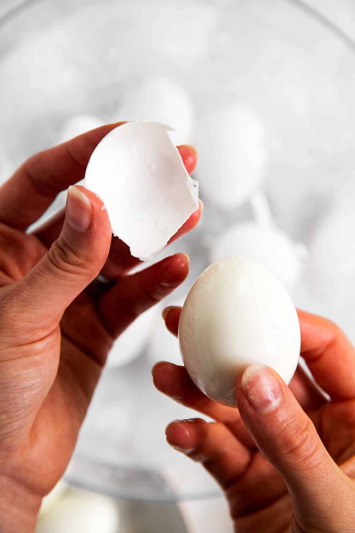 left hand holding egg shell with right hand holding peeled hard boiled egg