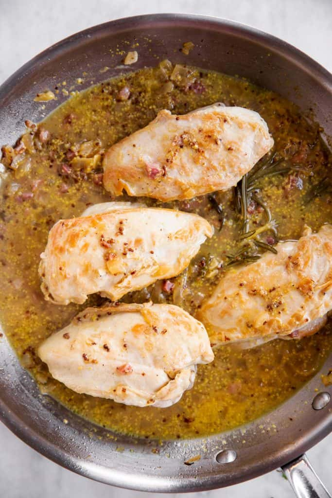 cooked honey mustard chicken in stainless steel skillet