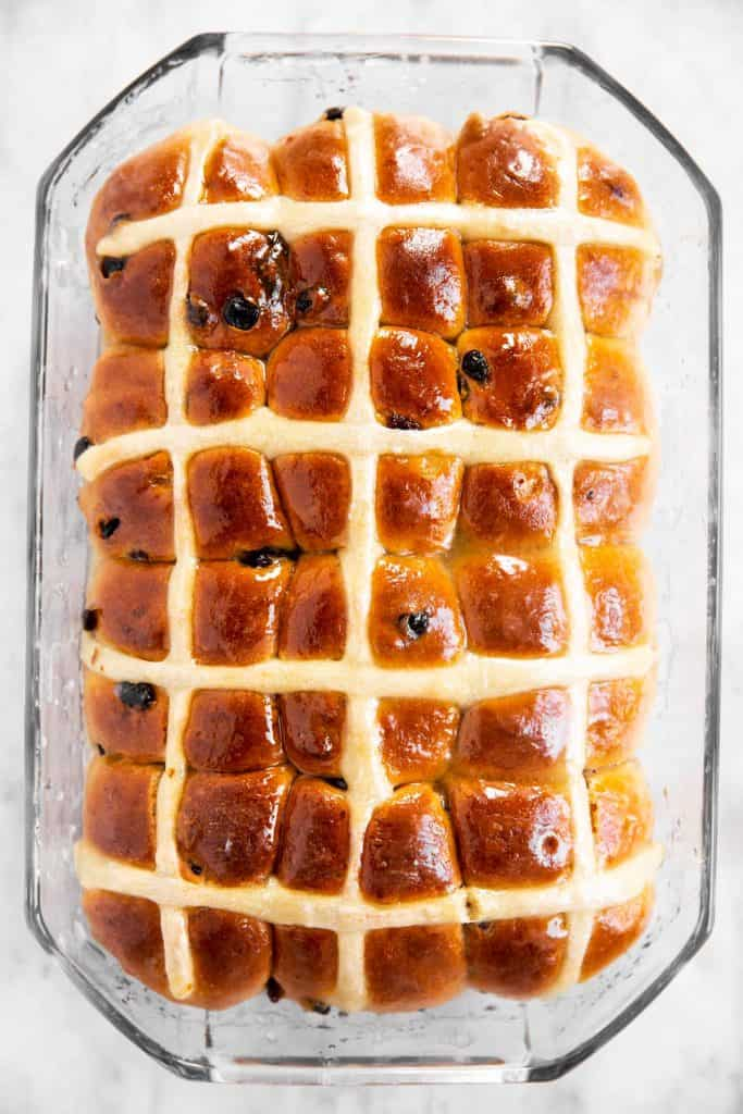 freshly baked and glazed hot cross buns in glass pan