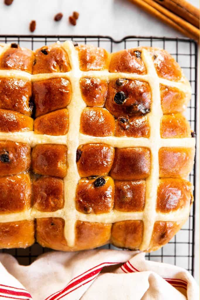 overhead view of hot cross buns on wire rack surrounded by a tea towel, raisins and cinnamons sticks
