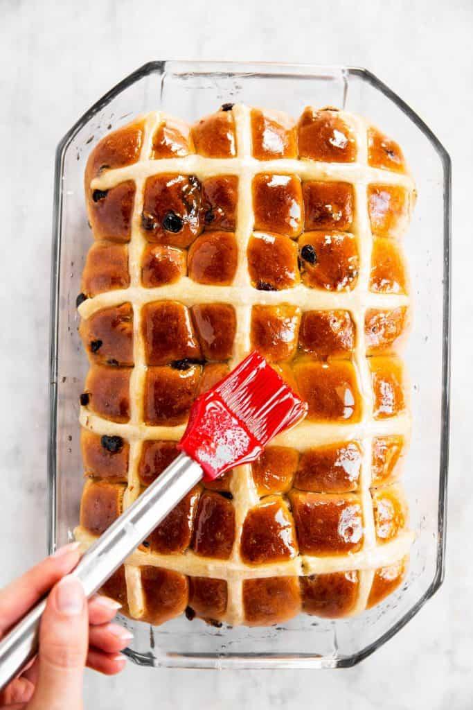 red pastry brush brushing orange glaze over baked hot cross buns in glass pan