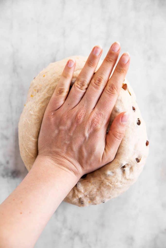 female hand kneading hot cross bun dough