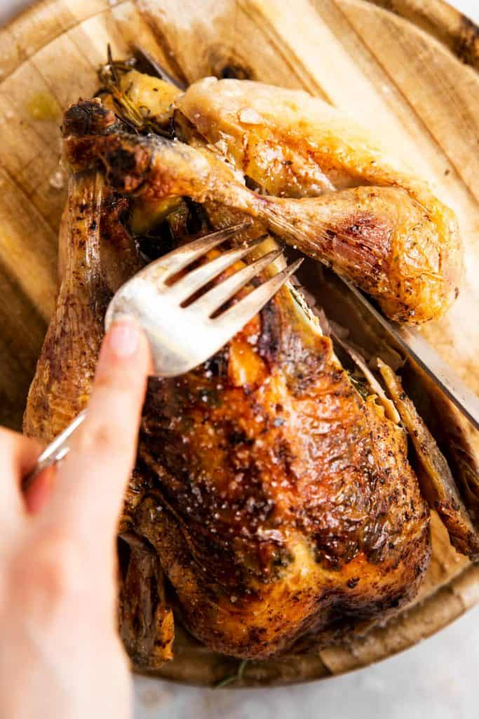 slicing a leg off a whole roasted chicken with a large fork and a carving knife