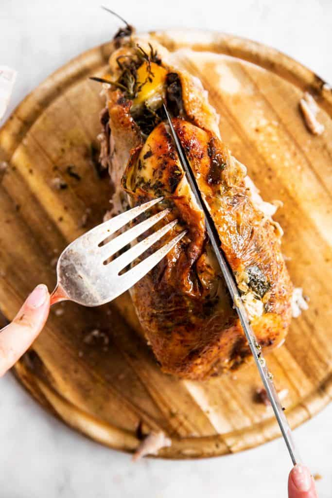 slicing apart the breast on a whole roasted chicken that's almost fully carved