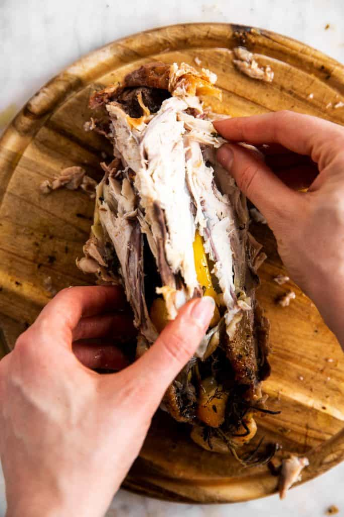 female hands picking meat off the carcass of a whole roasted chicken