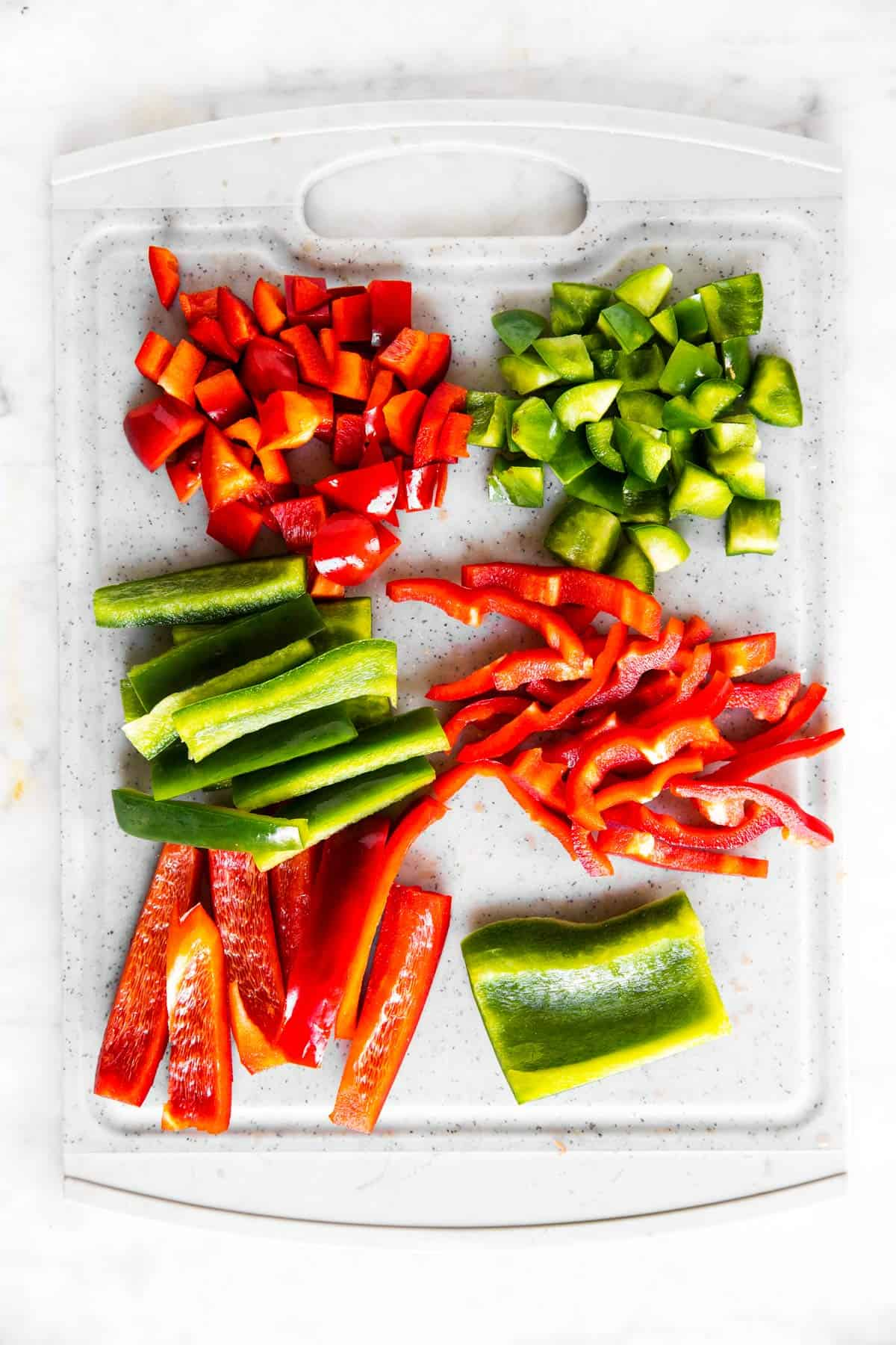 grey chopping board with red and green sliced bell pepper