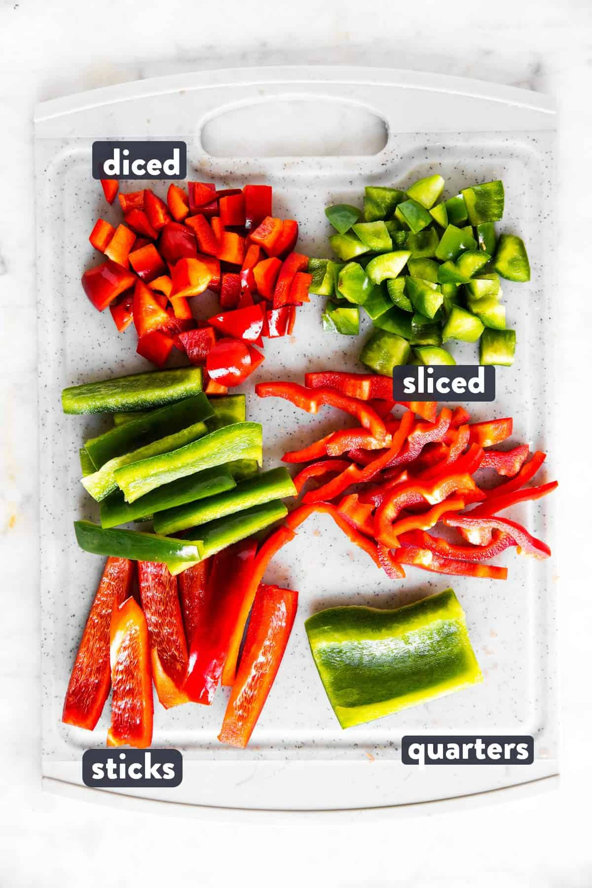 differently cut red and green bell pepper on grey chopping board with text labels