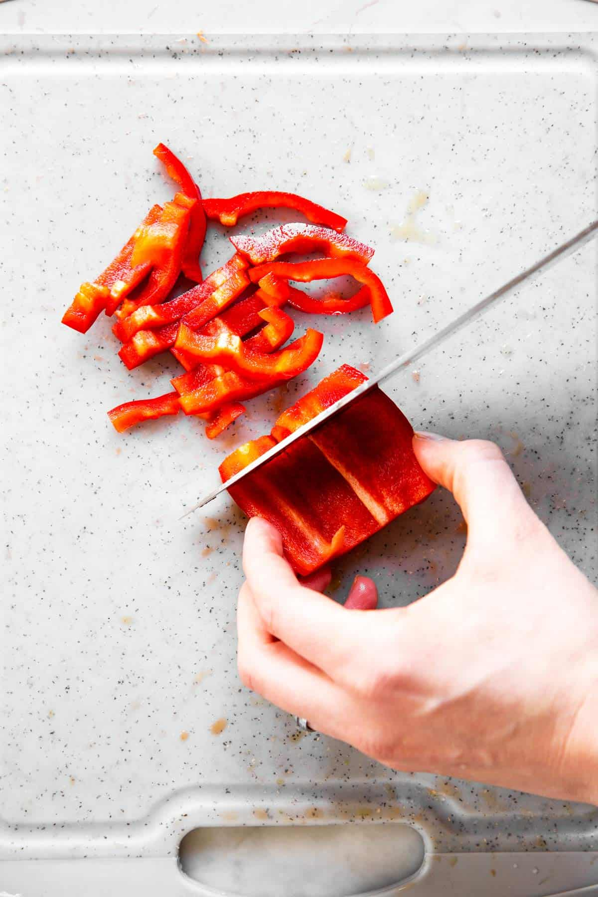 female hand slicing red bell pepper into thin slices
