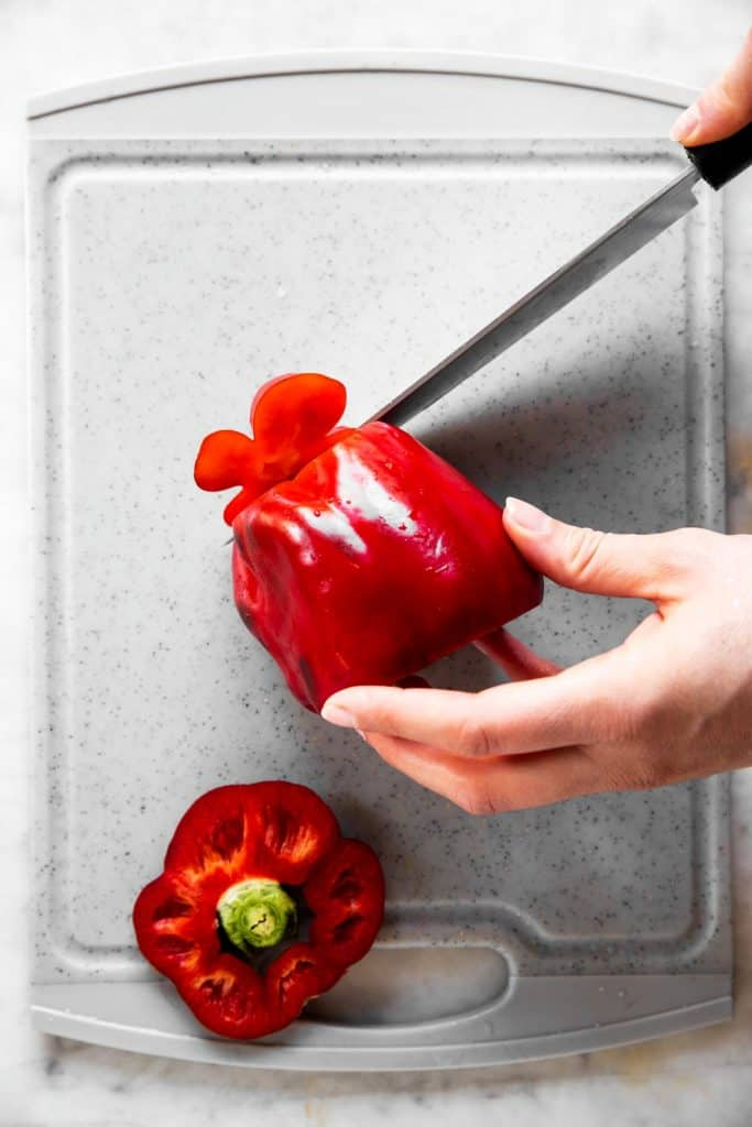 female hand slicing bottom off a red bell pepper