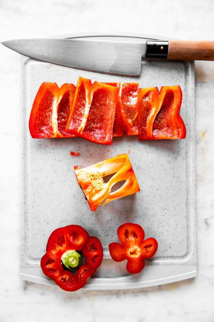 sliced bell pepper and core on grey chopping board with a chef's knife