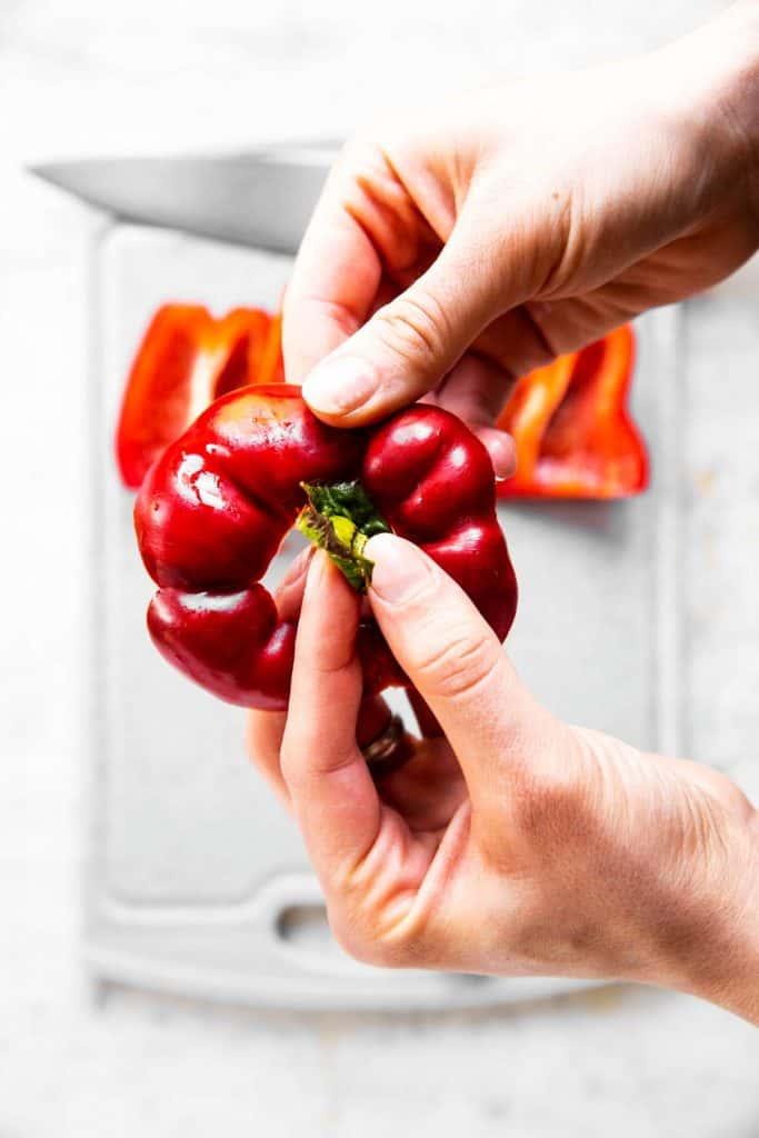 female hand removing green stem from bell pepper top