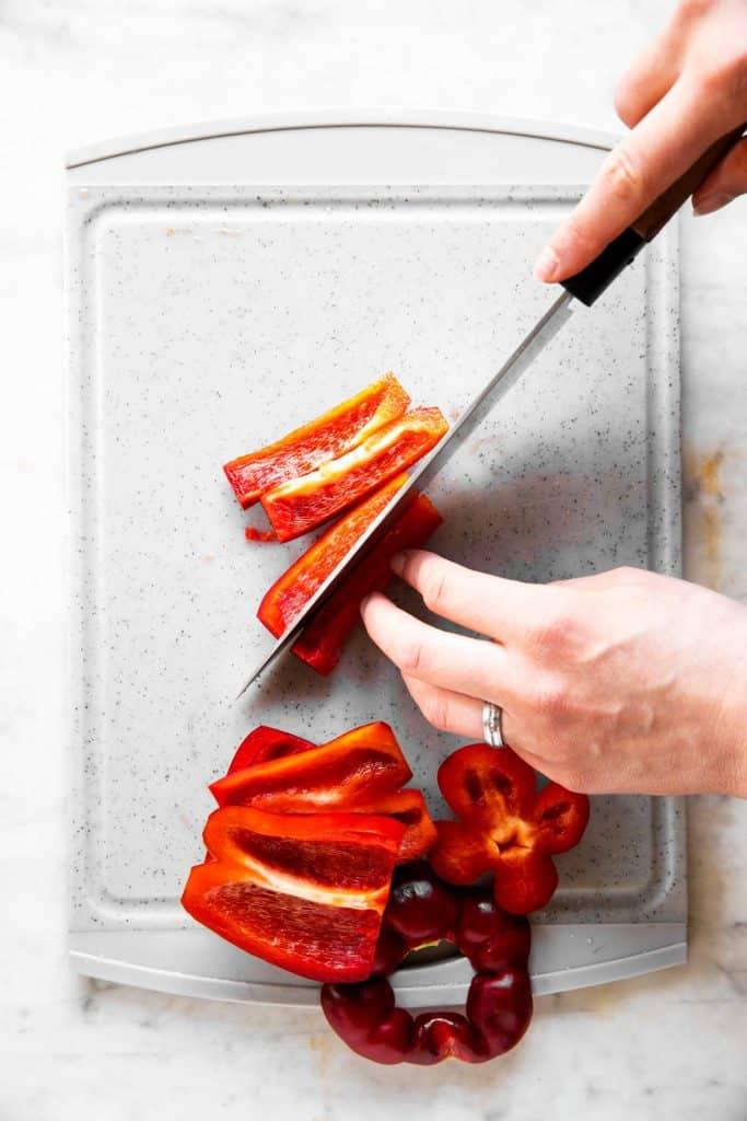 female hands slicing bell pepper into sticks