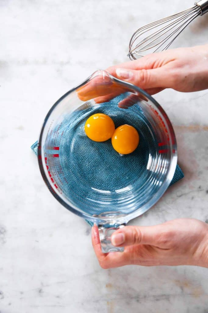 female hands placing glass measuring jug containing two egg yolks on blue cloth on marble surface