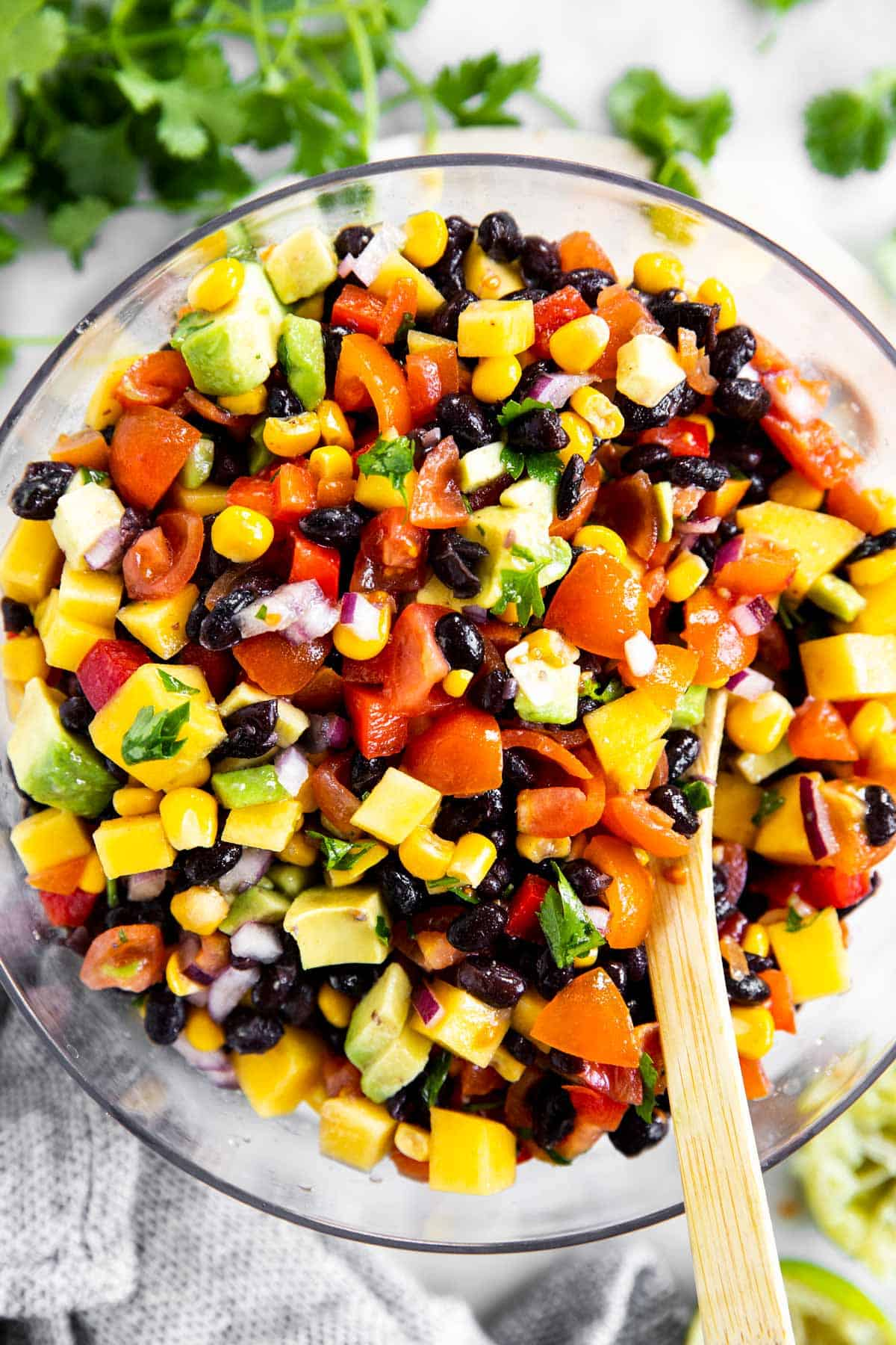 overhead view of glass bowl with mango black bean salsa surrounded by lime wedges and fresh cilantro
