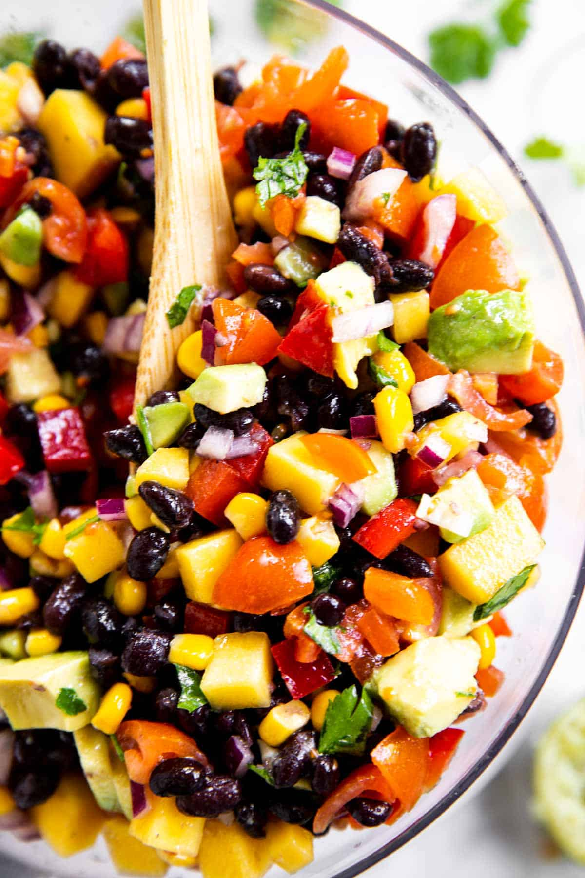 overhead close up view of mango black bean salsa in glass bowl with wooden spoon