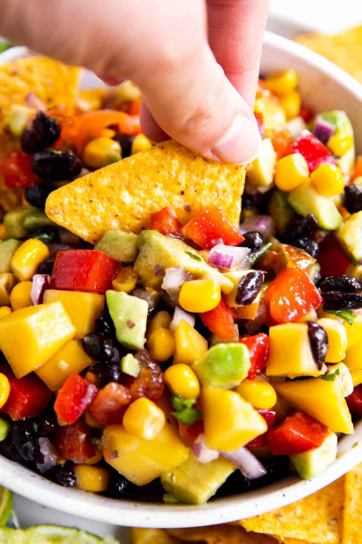 female hand dipping corn chip into mango black bean salsa