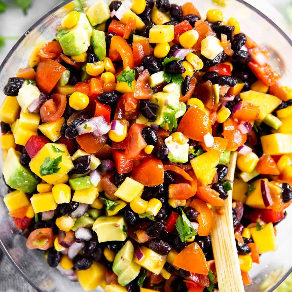 overhead photo of mango black bean salsa in glass bowl with wooden spoon
