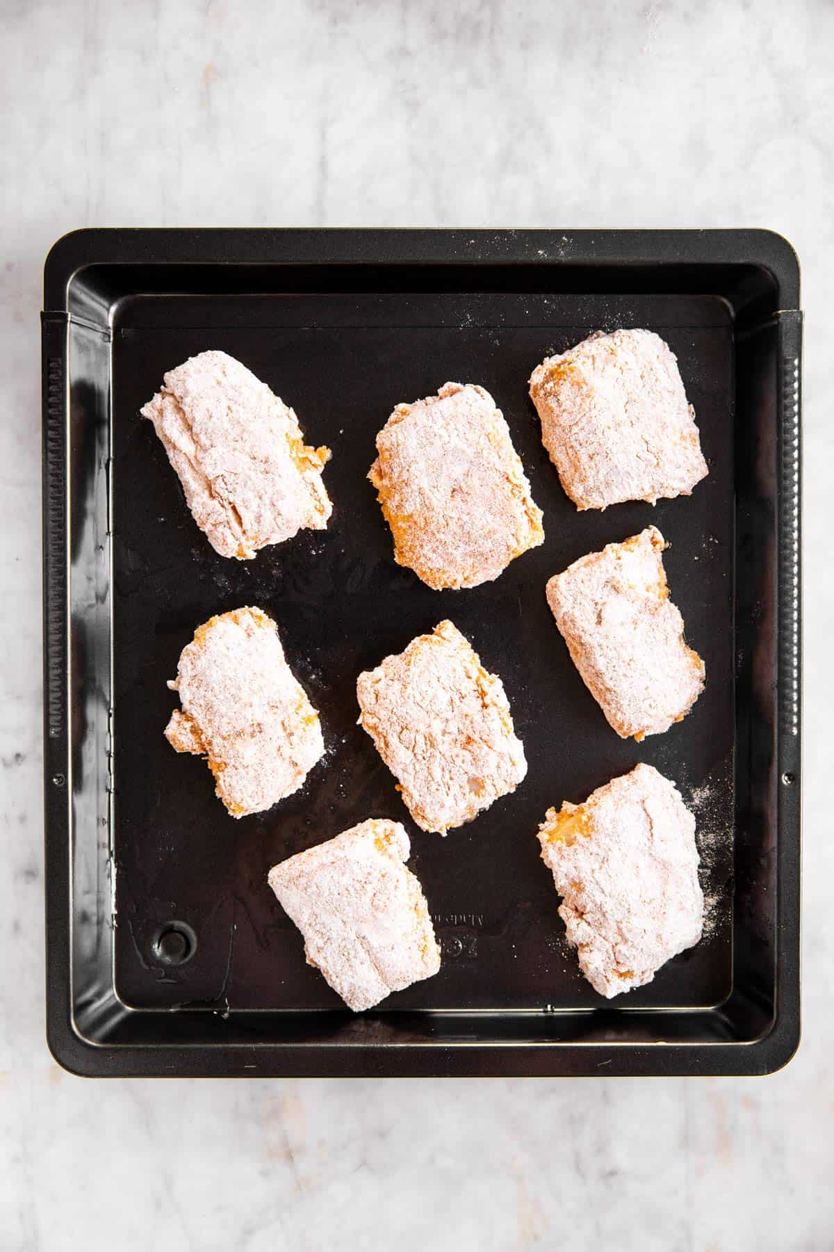 breaded fish pieces on black pan