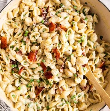 overhead view of pea and bacon pasta in white pot with wooden spoon