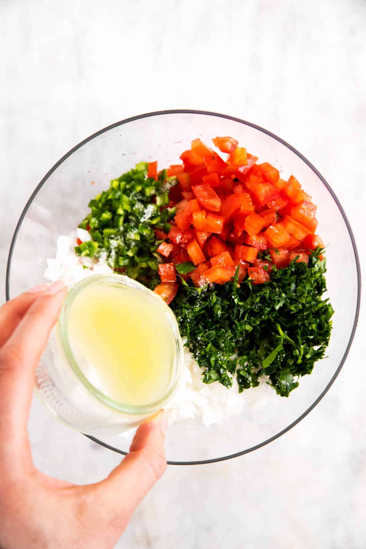 female hand pouring lime juice over ingredients for pico de Gallo in glass bowl