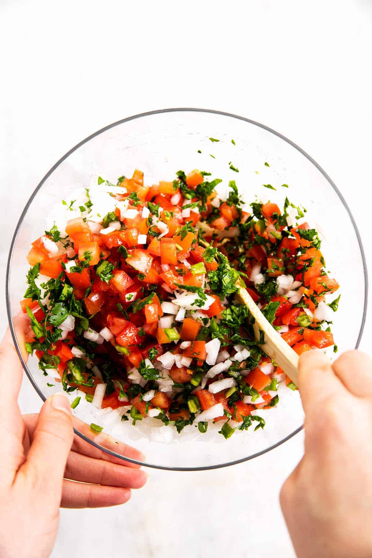 hands stirring pico de Gallo in glass bowl with wooden spoon