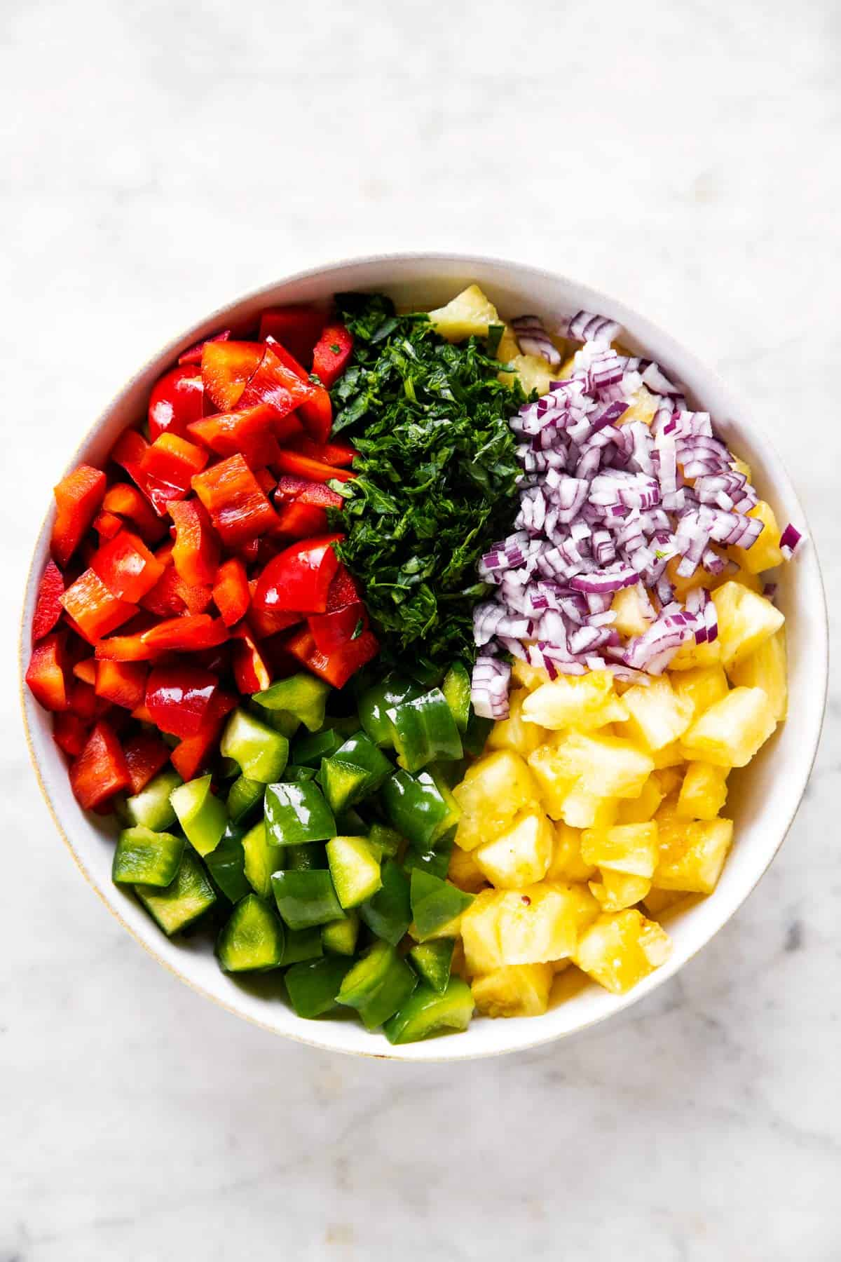ingredients for pineapple salsa in a white bowl