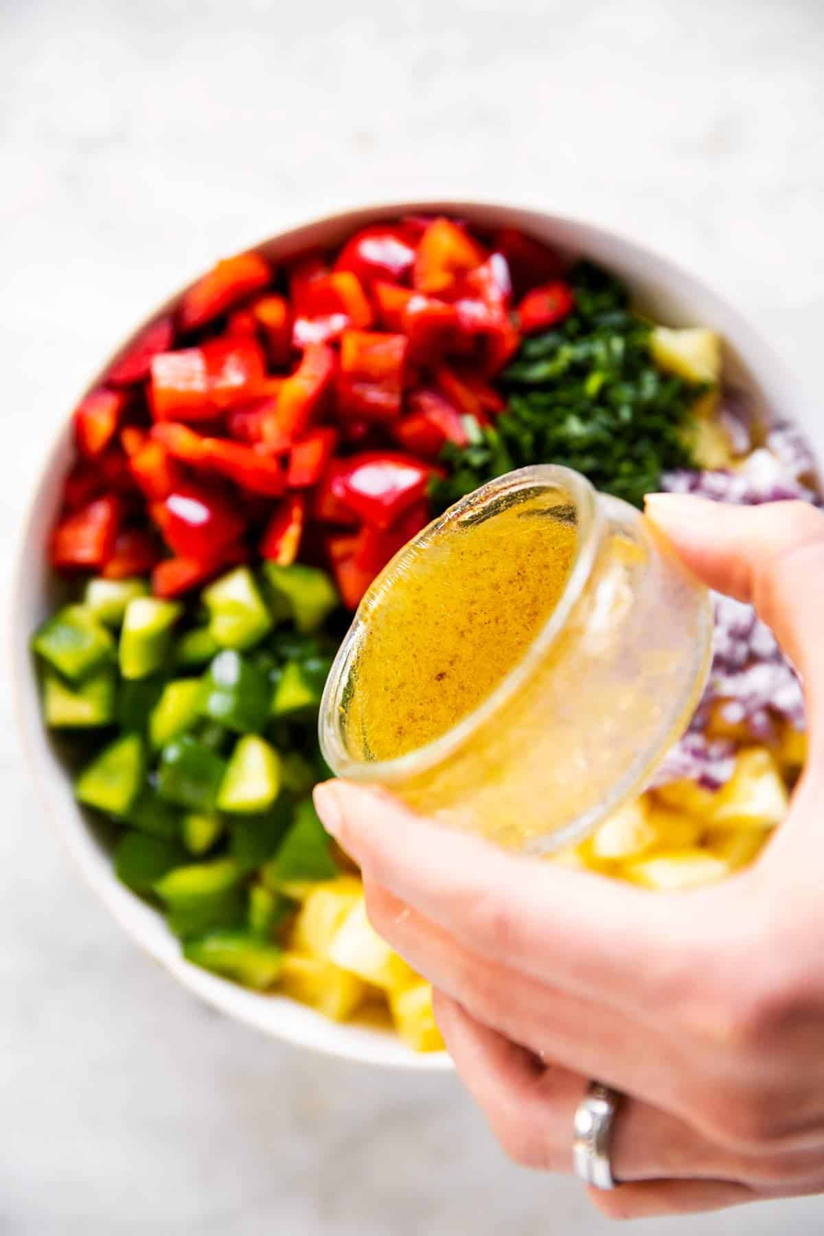 female hand pouring honey lime dressing over pineapple salsa ingredients