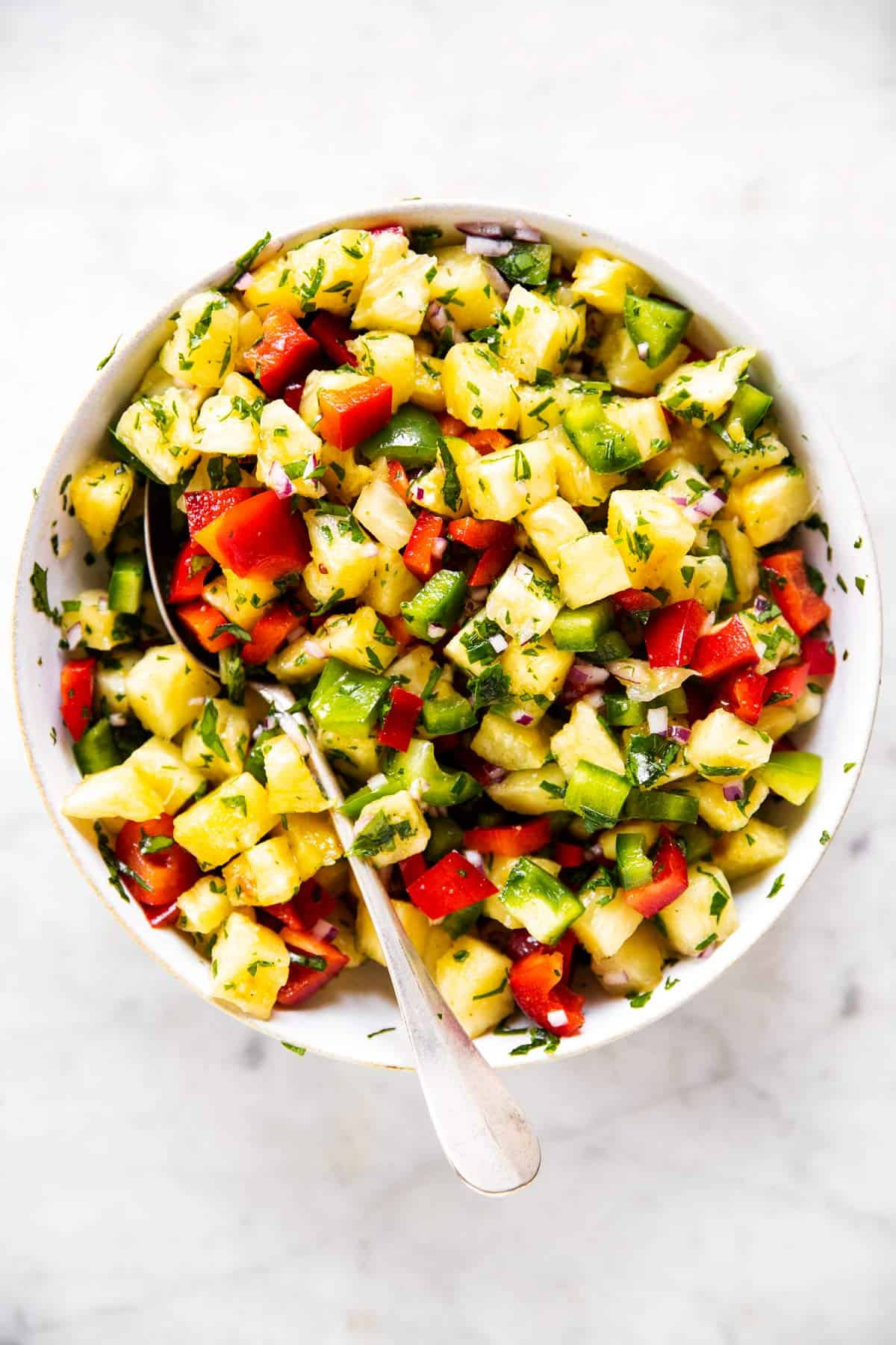 mixed pineapple salsa in white bowl with spoon stuck in
