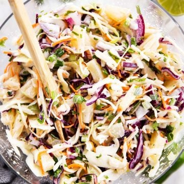 pineapple coleslaw in glass bowl with wooden salad tongs