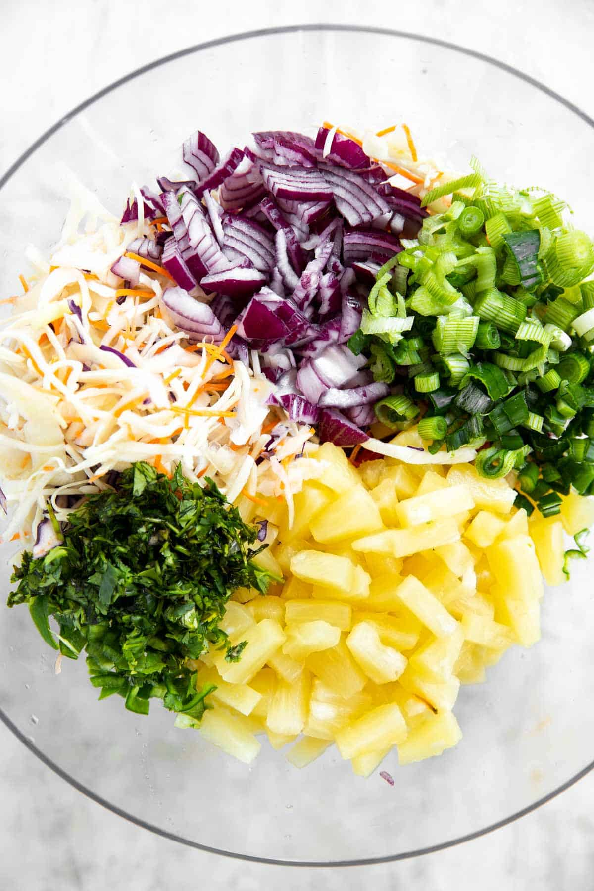 ingredients for pineapple coleslaw in glass bowl