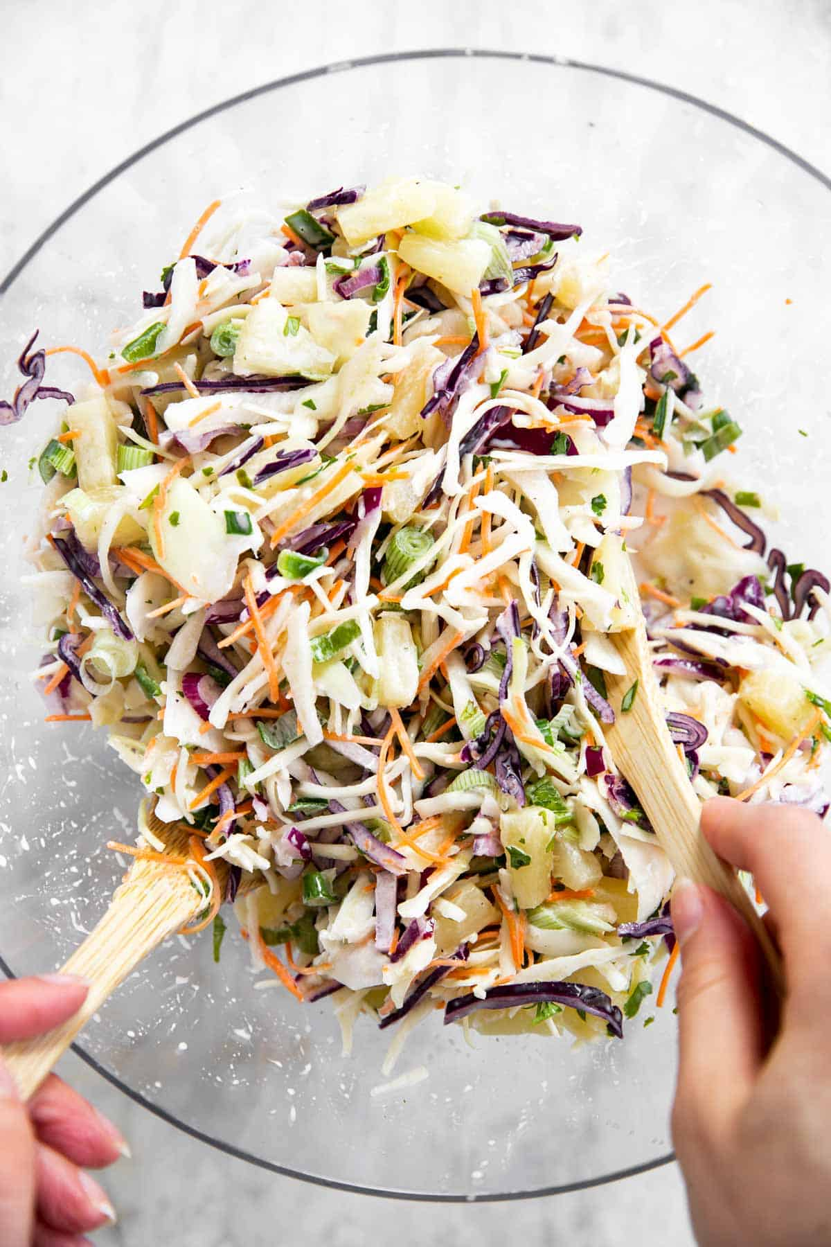 female hands using wooden salad tongs to toss pineapple coleslaw in glass bowl