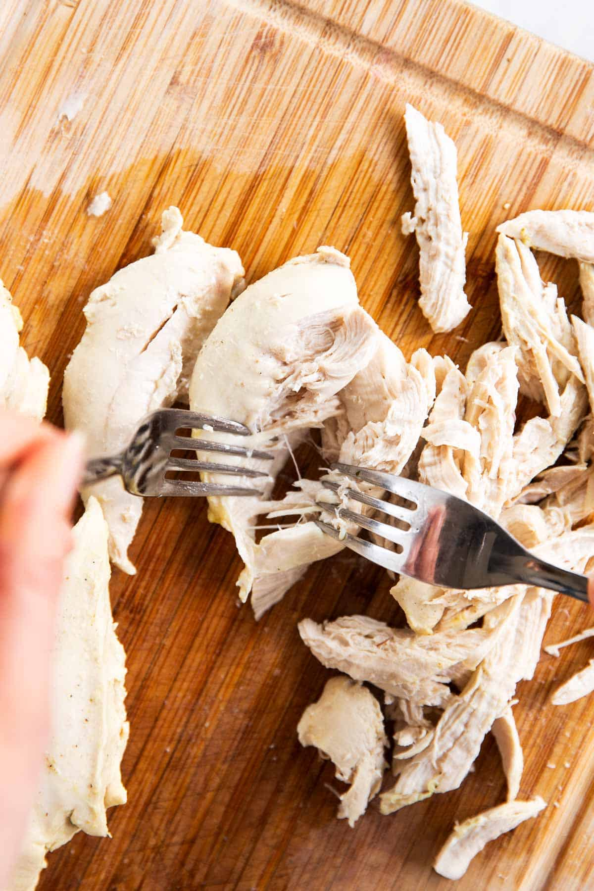 female hands using two forks to shred poached chicken breast on wooden board