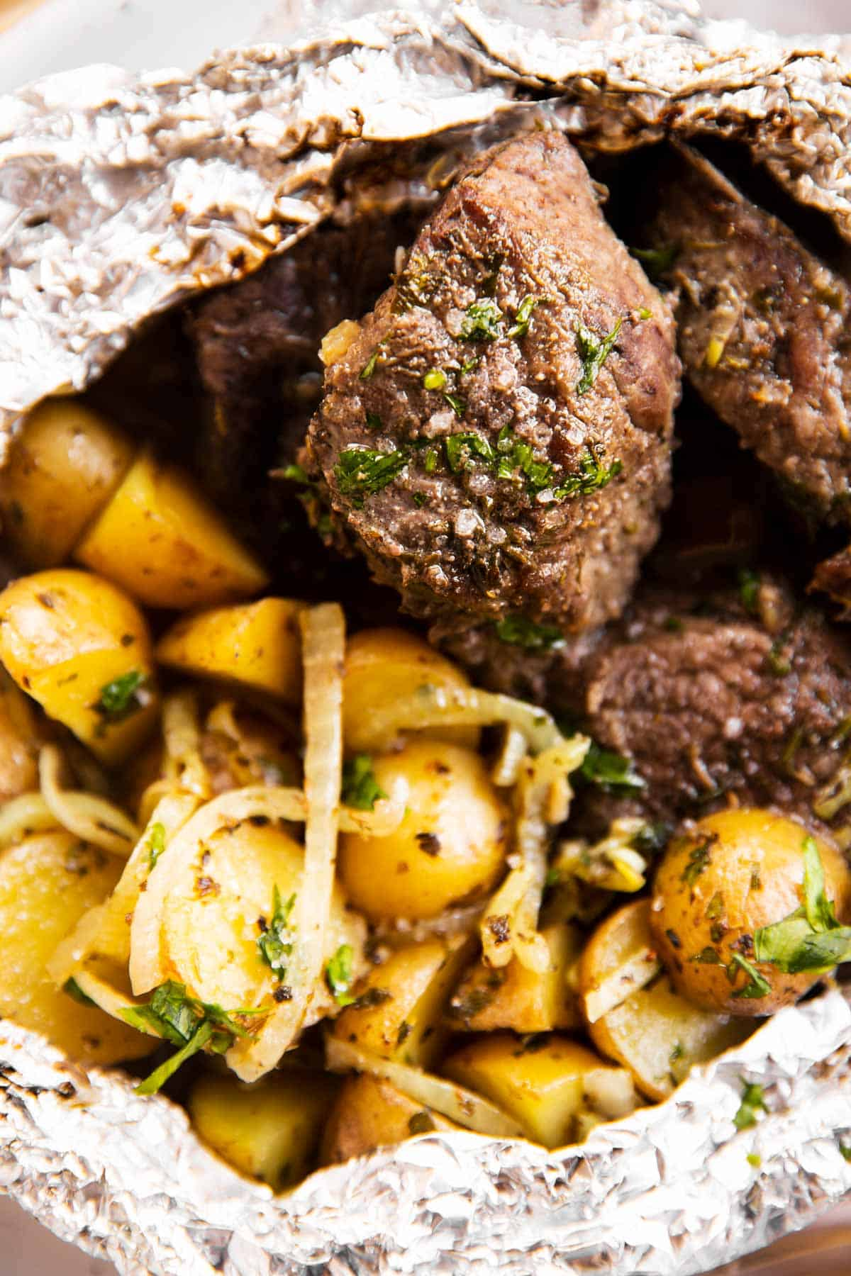 close up photo of steak and potatoes in foil packets