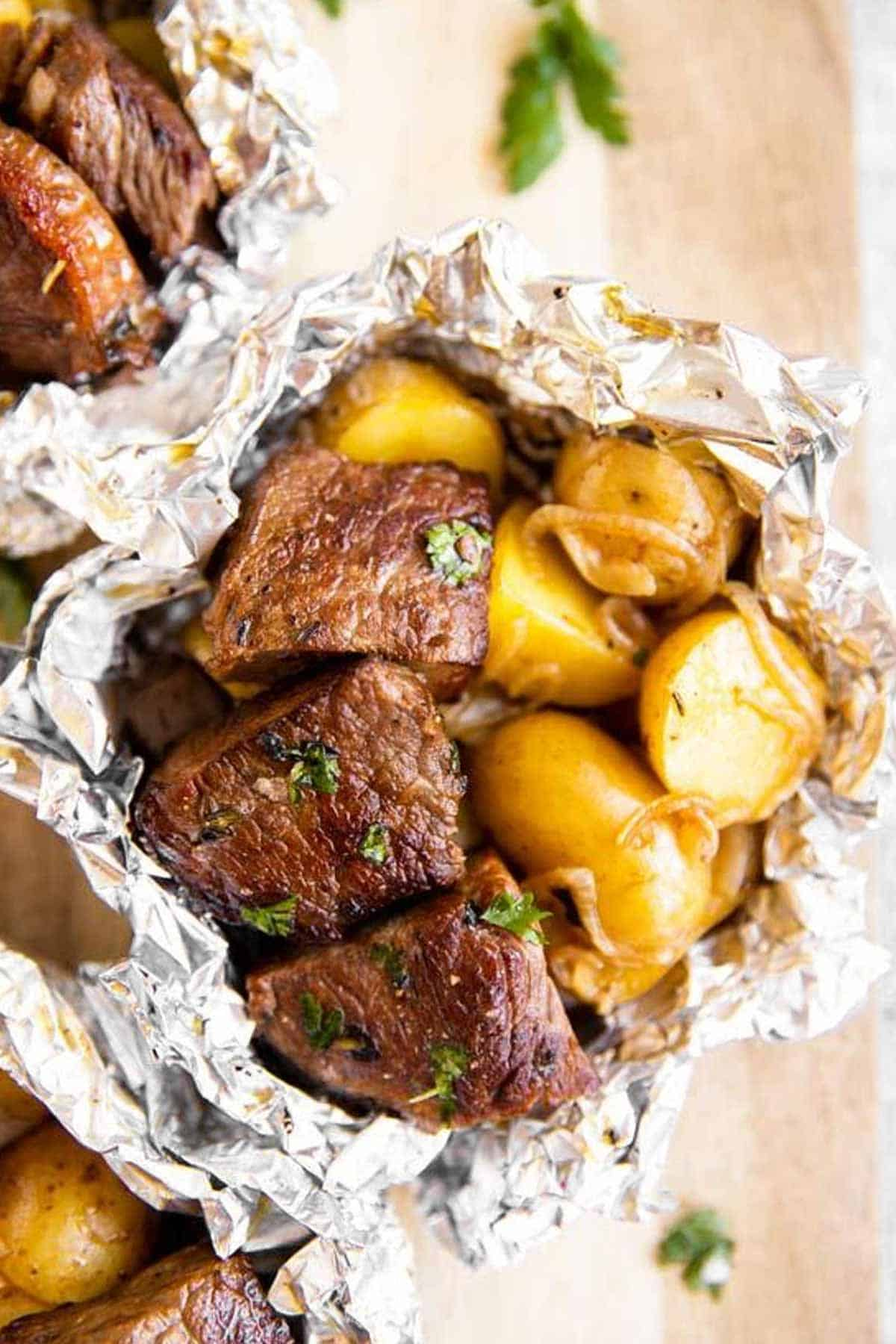 overhead view of a steak and potato foil packet on a wooden chopping board