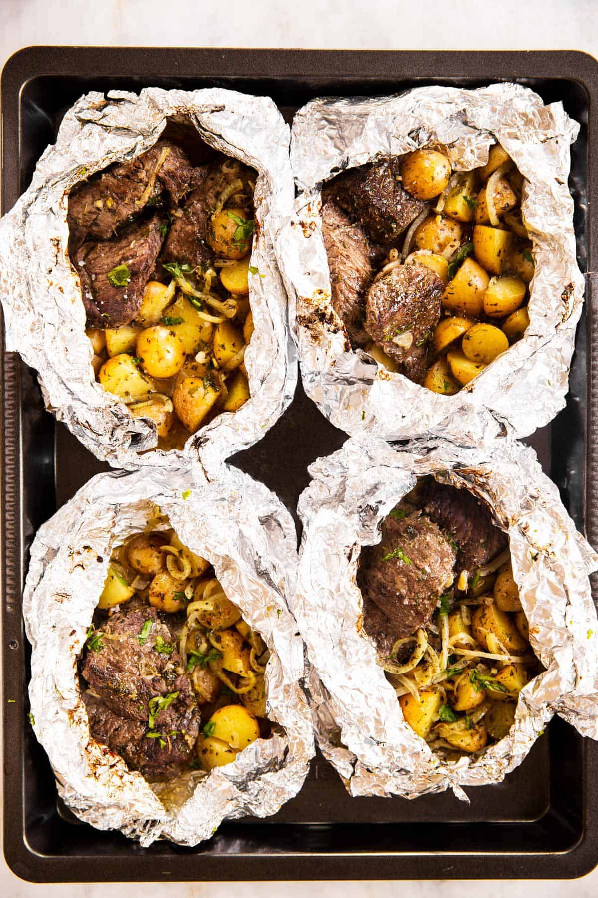 overhead view of four opened steak and potato foil packets on black sheet pan