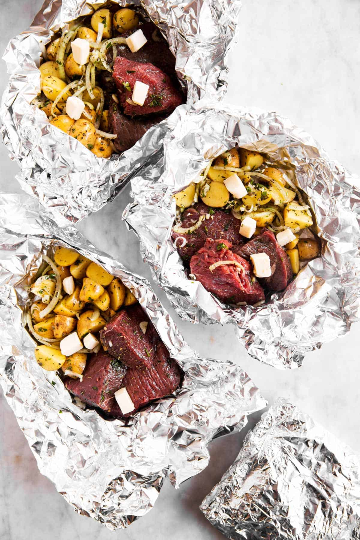 three unclosed steak and potato foil packets on marble surface