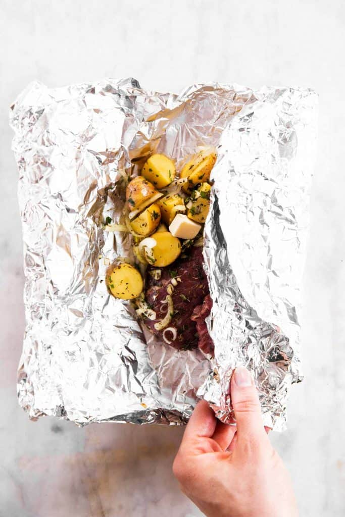 female hand folding foil over steak and potatoes